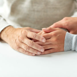 close-up-of-old-man-and-young-woman-holding-hands-PQFRP4A